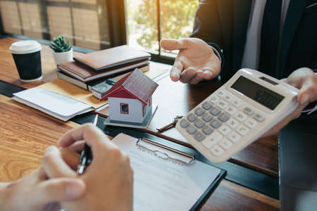 Agents are calculating the loan payment rate or the amount of insurance premiums for customers coming to contact the purchase of a new home at the office.