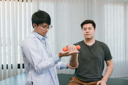 Asian physiotherapists are helping patients lift dumbbells for arm recovery.
