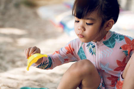 Asian kids girls playing in the sand on the beach while wearing a bathing suit.