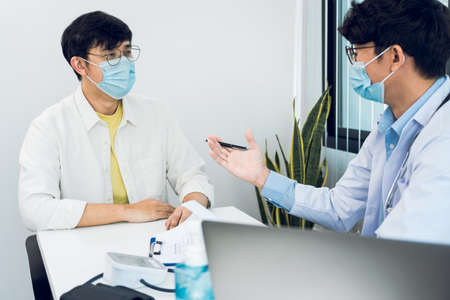 Doctors are explaining the treatment of a patient's illness while wearing a mask during the epidemic. Archivio Fotografico