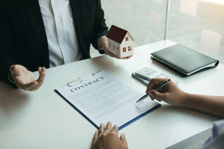 Hand of real estate agent passes the key to new homeowners in office with buyer house concept. 版權商用圖片