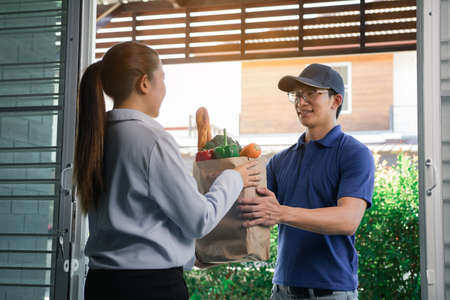 Delivery of an asian man handling a bag of food to a female customer at the door.