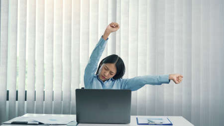 Young asian women stretch their muscles while sitting at the office to relax from the stress.