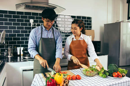 Two young asian couples are helping each other and enjoying cooking in the kitchen.