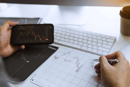 Investors use smartphones view investment graphs and record statistics on stock performance results for use in investment analysis.
