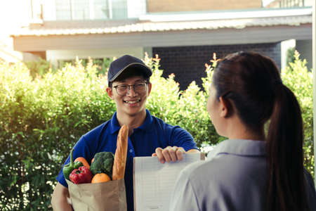 Supermarket food delivery staff deliver bags to female customers in front of the house.