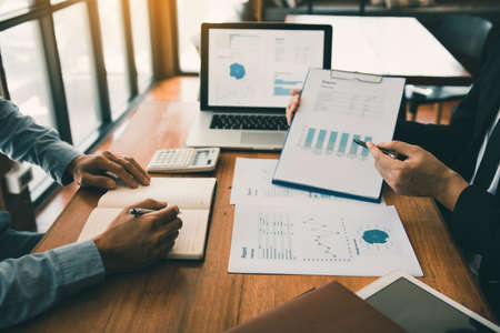 Business partnership pointing to the graph of the company financial statements report and profits earned during in the office.
