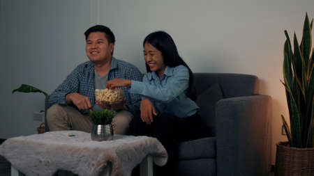 Asian couples watch movies on TV on weekends at night. 版權商用圖片