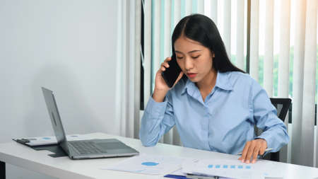 Asian manager is on the phone with an employee and is furious at the office office's faulty paperwork.