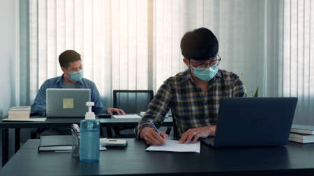 Asian colleague works while wearing a mask in the office during COVID-19.