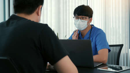 Doctors are explaining the treatment of a patient's illness while wearing a mask during the epidemic.