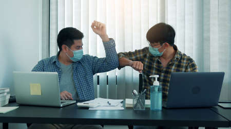 Asian colleagues in the office greet alternatives to avoid a handshake during the virus outbreak. 版權商用圖片