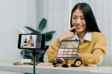 Asian teenage girls doing makeup vlogs and using a video mobile camera to record vlogs and publish them online at home. 版權商用圖片