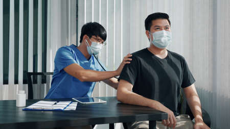 Asian doctor is using a stethoscope listen to the heartbeat of the patient.