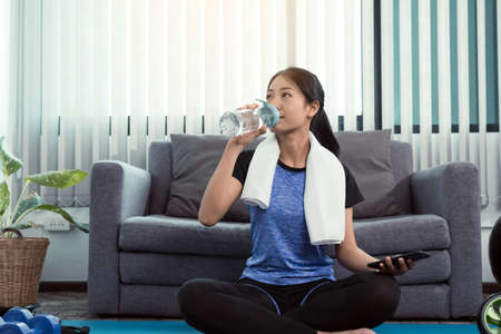 Asian woman sportswoman drinking from water bottle in her room after yoga exercise at home. 版權商用圖片