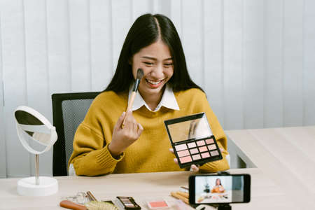 Young asian woman vlogging herself about beauty products with making a video for her blog on cosmetics using phone camera at home.