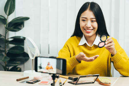 Young asian woman vlogging about cosmetics skin care items products on table with her video camera and demonstrates product use and reviews for her online blog channel. 版權商用圖片