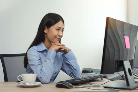 Asian woman software developers sitting in front of computers looking at computer codes on the screen. 版權商用圖片