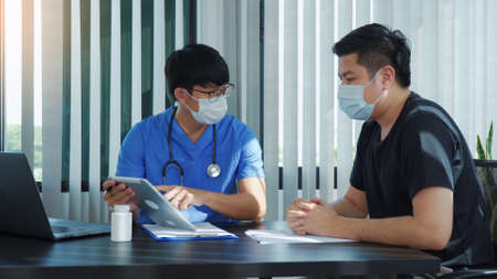 Doctors are explaining the treatment of a sick patient in tablets while wearing a mask during the virus outbreak.