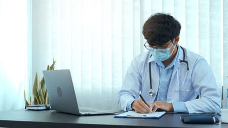 Doctor hand holding pen writing patient history list on clipboard about medication and treatment.