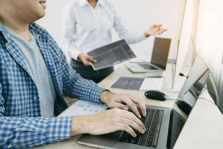 Two software developers are analyzing together about the code written into the program on the computer in office room.