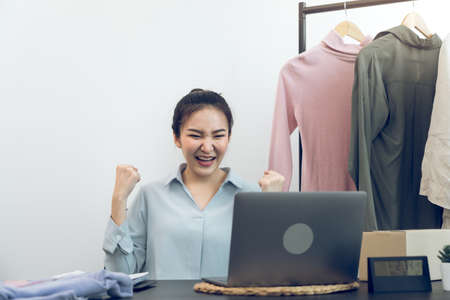 Young asian entrepreneurs are excited about hitting today's clothing sales target.