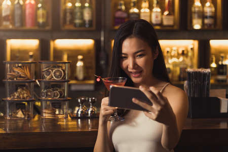 Asian woman taking a photo of herself while drinking whiskey at the bar. 版權商用圖片