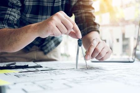 Interior designer or architect reviewing blueprints and holding pencil drawing on desk at home office.