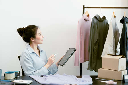 Asian entrepreneur is checking the remaining clothes in her warehouse via her tablet.
