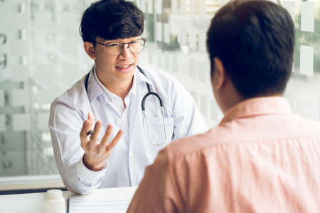 Asian doctor is examining the abnormal items of the body and diagnosing the disease in the paper with the medical report of the patient.