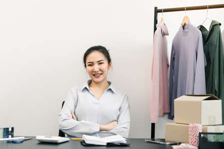 Asian entrepreneur sits on a chair and smiles, showing confidence.