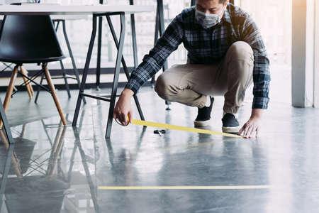 Male workers preparing masking tape to symbolize social distances. 版權商用圖片