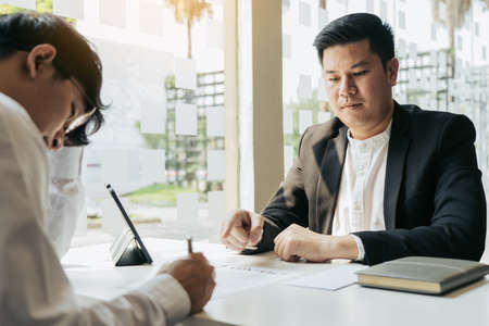 Male manager is talking or explaining about having to dismiss the employee while being handed out a resignation envelope to the employee. 版權商用圖片
