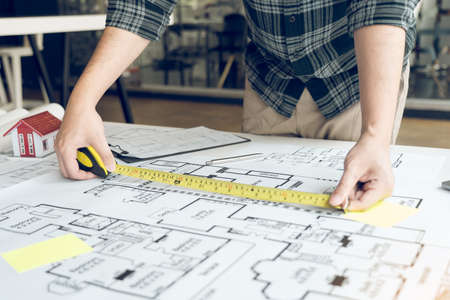 Architects are working on a new project while using a tape measure.