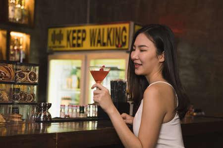 Asian women drinking cocktails and having fun at the bar at night. 版權商用圖片