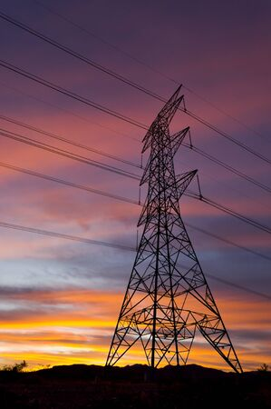 Power Pylons and Electricity transmission wires with clouds at sunset