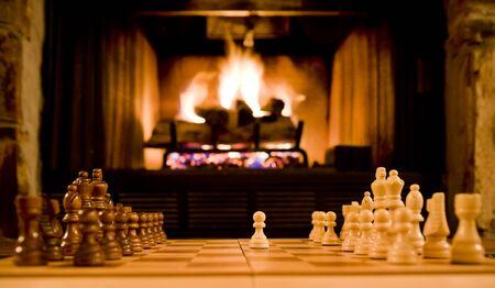 Schachbrett und Figuren mit Kamin im Hintergrund