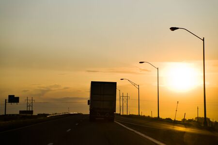 Big Rig Drives toward Sunset on US Interstate Highway