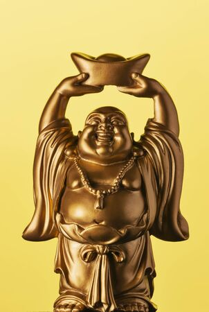 A small replica statue of The Buddha with a yellow background.  Yellow representing power, royalty, and prosperity. It also represents summer