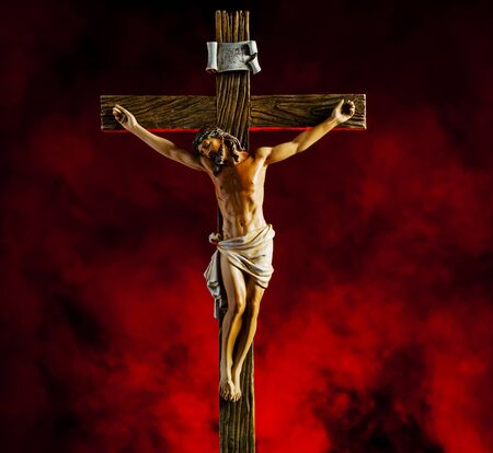 A small statue of Jesus Christ on the Cross with red smoke Stock Photo