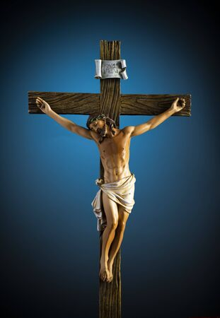 A small statue of Jesus Christ on the Cross on blue with vignette