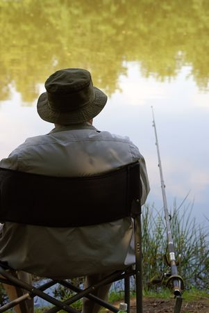enjoys: An old man enjoys a perfect day of fishing                    Stock Photo