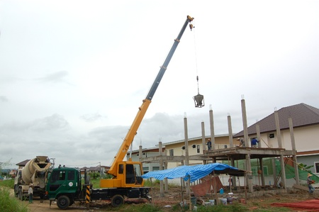 The basket of concrete was deliver to construction site by crane truck  photo