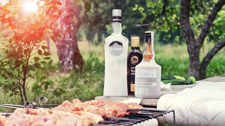 Belarus. Minsk region. July - 25.2017: Alcohol and meat. Picnic in the village. Belarusian alcohol - vodka Bulbash, Balm Black witch doctor, black rum Diablo
