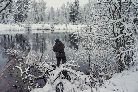 Fisherman is fishing on the winter river.