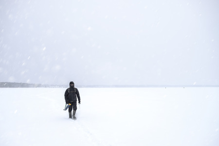 Fisherman out into the snowy expanse of the lake. Winter fishing.