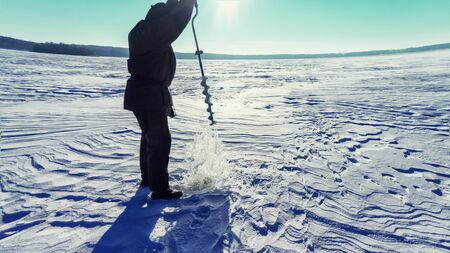 Fisherman drills the ice. Winter fishing.