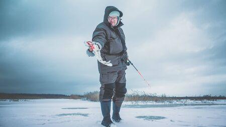 Fisherman caught a pike on ice fishing. Stock Photo