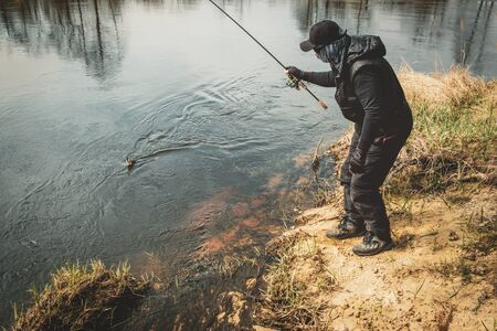 Fisherman caught a fish on the river bank.