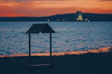 Silhouette gazebo on the beach against the setting sun.